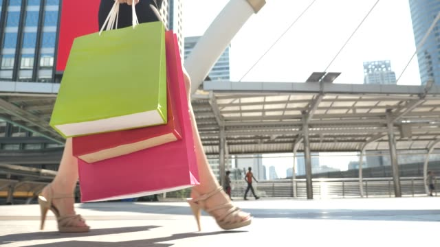leg of young woman walks with shopping bags - borsa della spesa video stock e b–roll