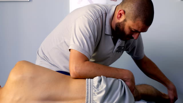 leg physiotherapy:physiotherapist moves the patient's leg - physical therapy стоковые видео и кадры b-roll