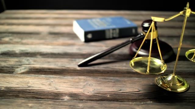 弁護士と弁護士のオフィスで法的な小道具。裁判官は、正義と弁護士の本の規模を与えた。パン 4k フッテージビデオ - 金づち点の映像素材/bロール