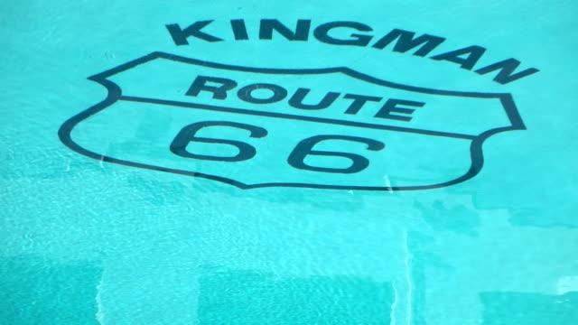stockvideo's en b-roll-footage met legendarische kingman route 66 kop in het zwembad in slow motion 250fps - arizona highway signs