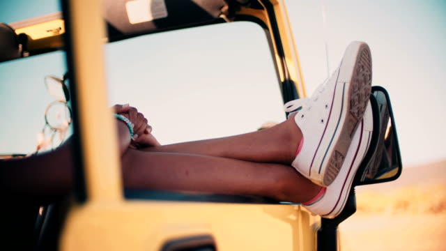 legs and feet sticking out of car window on road trip video