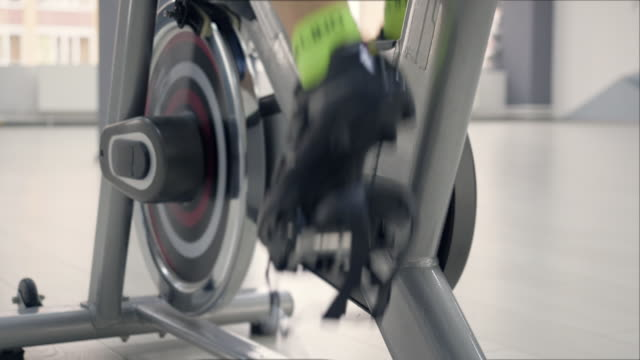 Legs are exercising pedals on the stationary bicycle. Legs are exercising pedals on the stationary bicycle. Legs close-up. exercise bike stock videos & royalty-free footage