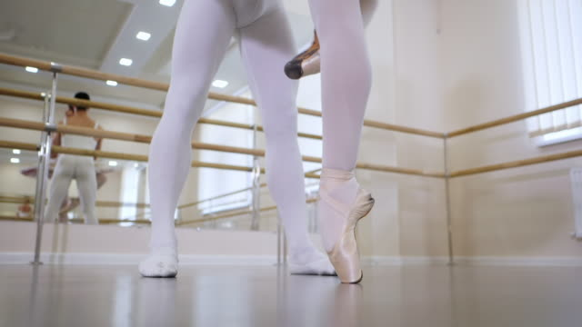 Legs close up. Rehearsal in the ballet hall or studio with minimalism interior. Young professional sensual dancer's couple in beautiful costume dancing together. Slow motion