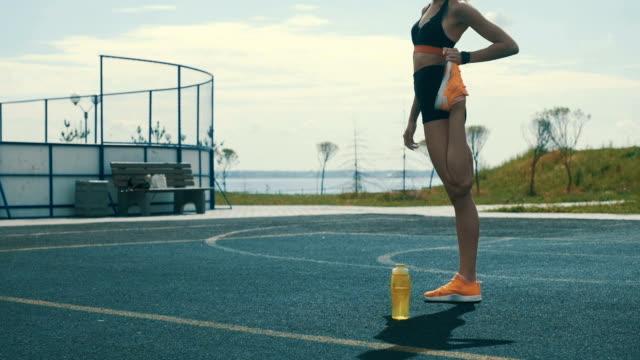 vidéos et rushes de exercices de jambes pour le jogging au stade d'été - joggeuse