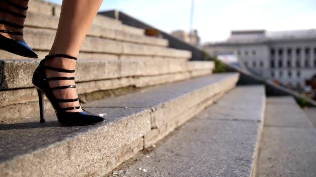 vídeos de stock, filmes e b-roll de pernas de salto alto descendo escadas na cidade - salto alto