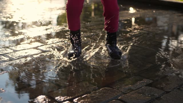 Legs in rubber boots jump through the puddles, spray scatter,slow motion. video