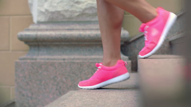 Legs in sport shoes walking down stairs in slow motion video