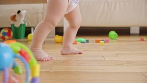 vídeos de stock e filmes b-roll de slo mo legs of a barefoot baby walking in the living room - brinquedo