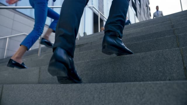 SLO MO TS Legs of a business man wearing black shoes and business suit walking up the stairs outside the  business building
