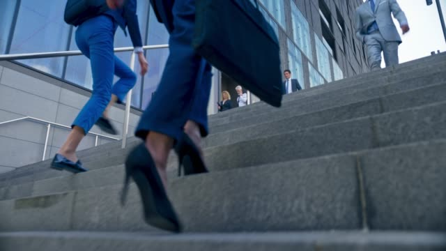 TS Legs of a business woman in high heels walking up the stairs in front of a modern business building amongst other people