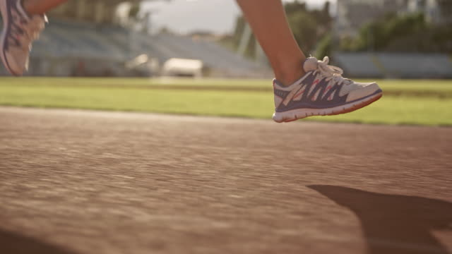 日当たりの良いスタジアムで実行している白人女性アスリートの slo mo ts 足 - 陸上競技点の映像素材/bロール