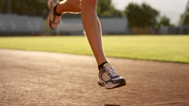 vidéos et rushes de slo mo jambes d'un homme de race blanche en cours d'exécution dans le stade au coucher du soleil - athlétisme