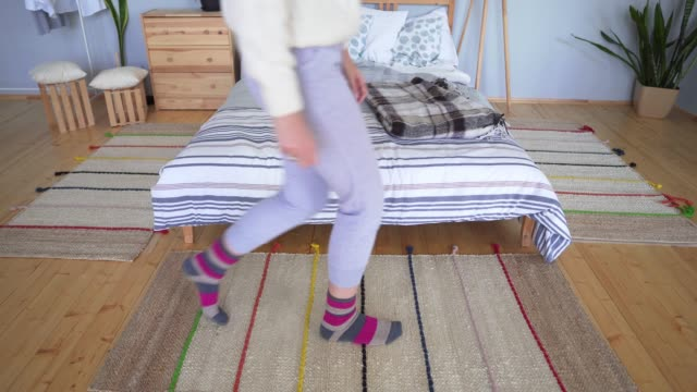 vídeos de stock e filmes b-roll de legs of a crouching woman on a scandinavian-style carpet. holidays, christmas, comfort and hygge - hygge
