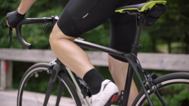 slo mo ts legs of a cyclist pushing the pedals on the road bike up a mountain road - ciclismo su strada video stock e b–roll