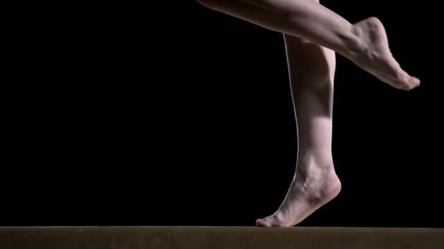 SLO MO Legs of a female gymnast doing a turn on the balance beam