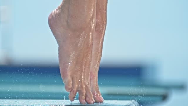 slo-mo-beine eines weiblichen hohen tauchers vom sprungbrett springen - sprung wassersport stock-videos und b-roll-filmmaterial