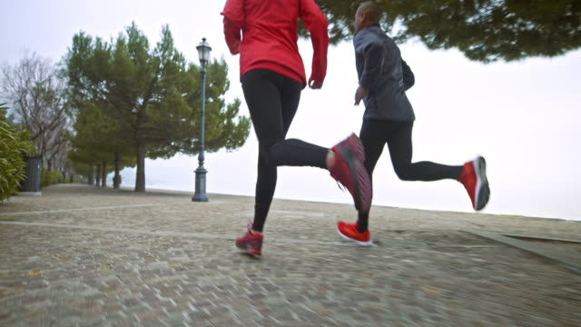 SLO MO Legs of a male and female runner running on a footpath along the sea in the early morning