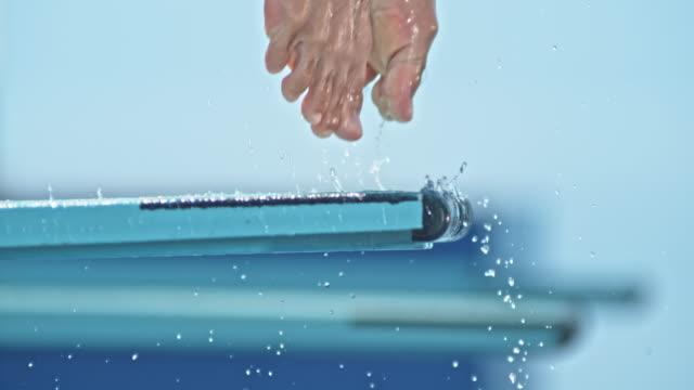 slo-mo-beine eines männlichen hohe tauchers vom sprungbrett springen - sprung wassersport stock-videos und b-roll-filmmaterial