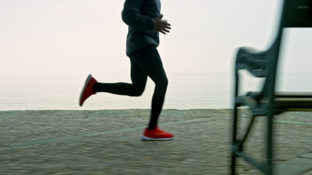 SLO MO TS Legs of a man running on a footpath along the sea on a foggy morning