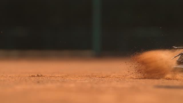 vídeos de stock e filmes b-roll de legs of a tennis man sliding on the ground, ultra slow motion - ténis calçado desportivo