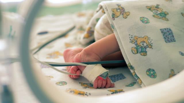 beine eines kleinkindes, das in einer krankenhauseinheit in einer nahaufnahme liegt - medizinisches untersuchungsgerät stock-videos und b-roll-filmmaterial
