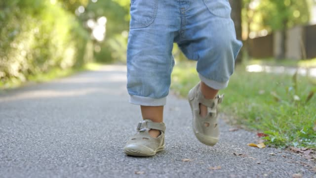 slo mo ds legs of a toddler walking on a sidewalk - jeans video stock e b–roll