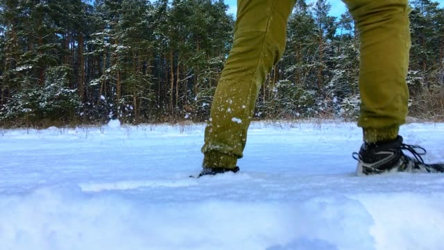 Legs of a tourist pass through the snow in slow motion video