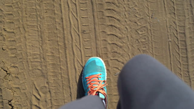 legs of a traveler from above. legs in sports krosovkah are lying along the deserted road. on the sand there are traces of the tires of cars. active rest in the journey. hiking - city walking background video stock e b–roll