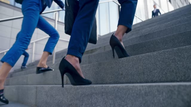 SLO MO TS Legs of a woman in a business suit and high heels walking up the stairs outside a modern office building