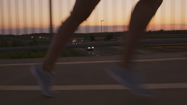 SLO MO Legs of a woman running across a bridge at dusk Slow motion shot of legs of an unrecognizable female runner running across a bridge over a highway at dusk. human foot stock videos & royalty-free footage