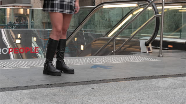 Legs of a young woman at the entrance to the subway.
