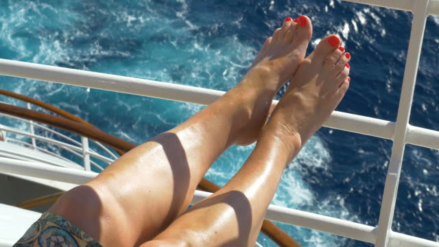 Legs of a young woman at the railing of a cruise ship