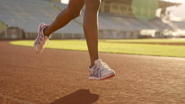 slo mo ts legs of an african-american woman running in stadium at sunset - track and field stock videos and b-roll footage