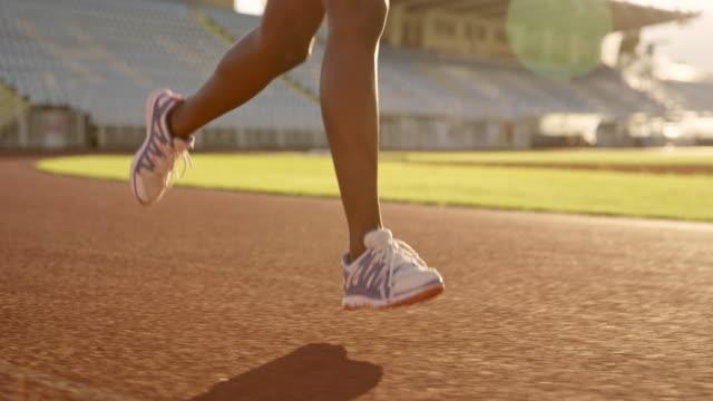 SLO MO TS piernas de una mujer afroestadounidense corriendo en el estadio al atardecer - vídeo