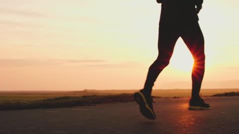 vídeos de stock e filmes b-roll de ms legs of an unrecognizable jogger on country road - correr
