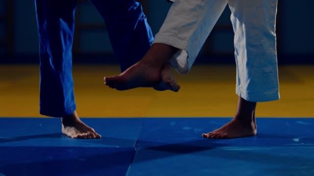 tatami üzerinde sporcuların bacaklar. güreşçiler ayaklarıyla süpürme yapar. aşağıdan görüntüleyin. - karate stok videoları ve detay görüntü çekimi