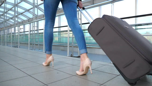 Legs of business woman going through hall of terminal with her luggage. Girl in high heels stepping and roll suitcase on wheels. Concept of work trip or travel. Slow motion Close up Legs of business woman going through hall of terminal with her luggage. Girl in high heels stepping and roll suitcase on wheels. Concept of work trip or travel. Slow motion Close up human foot stock videos & royalty-free footage