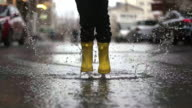istock Legs of child in yellow rubber boots jumping in puddles 1216473875