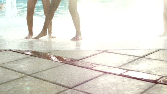 Legs of children playing at water park pool fountain