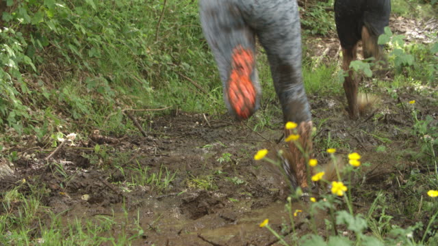Legs of competitors running through mud on an assault course video