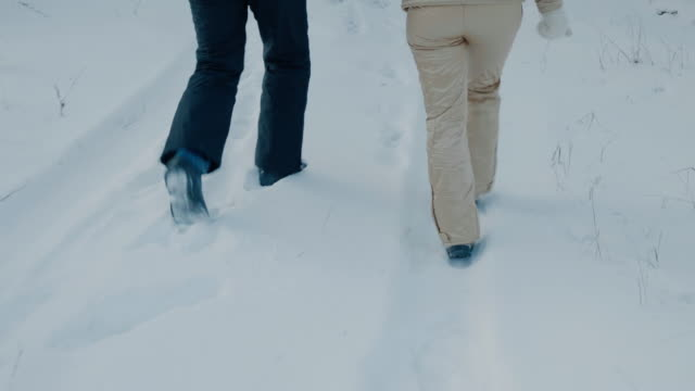 Legs of couple walking together in snow in winter forest
