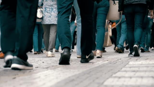 stockvideo's en b-roll-footage met benen van menigte mensen lopen op straat in slow motion - oversteekplaats