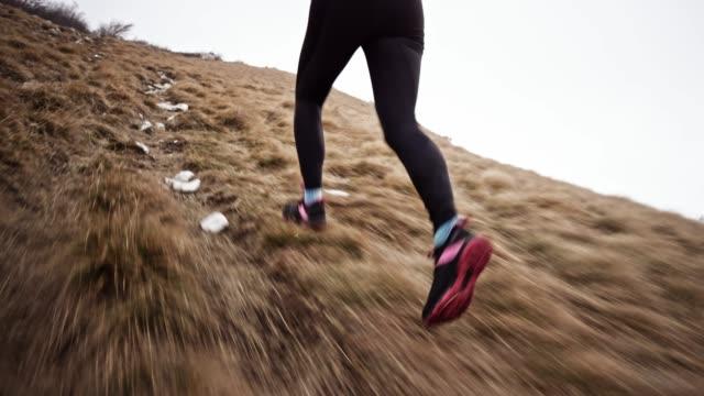 gambe di runner femminile che corrono su un pendio di montagna erboso in una giornata nuvolosa - atletico video stock e b–roll