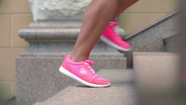 Legs of fitness woman and man in sport shoes walking up steps video