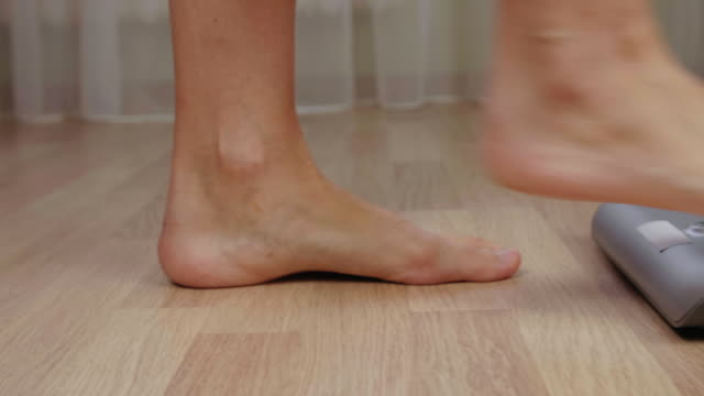 Legs of fitness women stepping to weighting scale for body mass control close up Legs of fitness women stepping to weighting scale for body mass control close up. Human foot standing on weight scale for body measuring. Diet and weight loss concept stepping stock videos & royalty-free footage