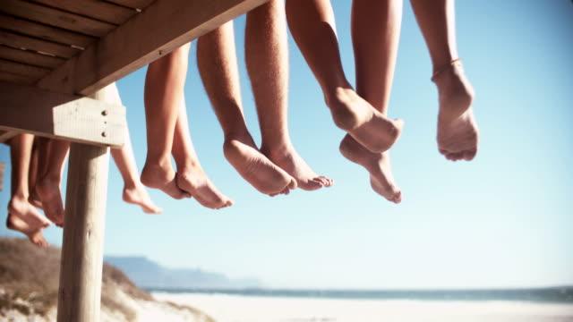 Legs of friends sitting on a beach boardwalk together