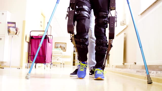 Legs of invalid in orthosis walking with support of two walking cane Close up legs of disable man in the robotic exoskeleton walking through the corridor with support of a doctor. Then camera moving to the faces. Both smiling. prosthetic equipment stock videos & royalty-free footage