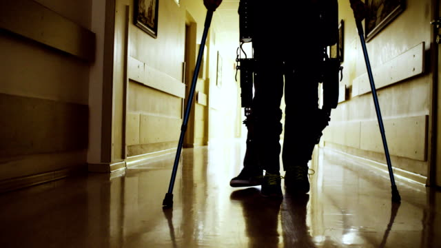 legs of invalid in robotic exoskeleton walking through the corridor - fisioterapia video stock e b–roll