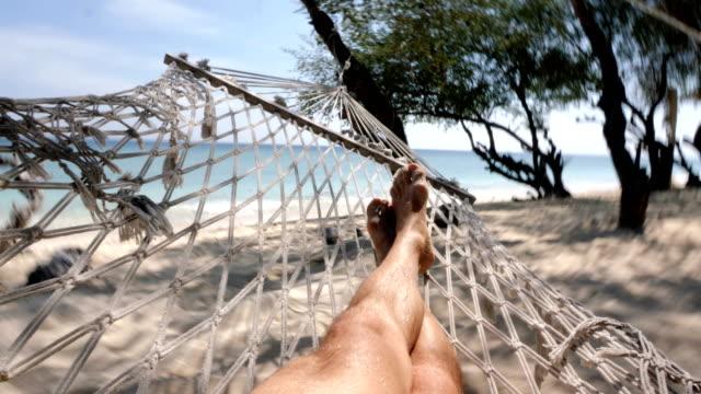 legs of man swinging at the beach in gili trawangan island in bali - amaca video stock e b–roll
