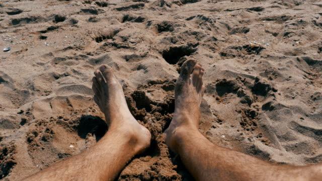 Beine der Männer am Strand liegen in der Nähe von Meer, POV – Video